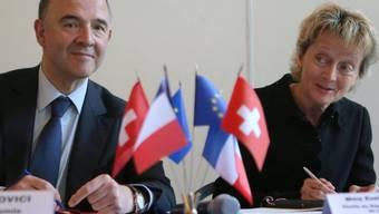 Pierre Moscovici und Bundesrätin Widmer-Schlumpf beim Unterzeichnen