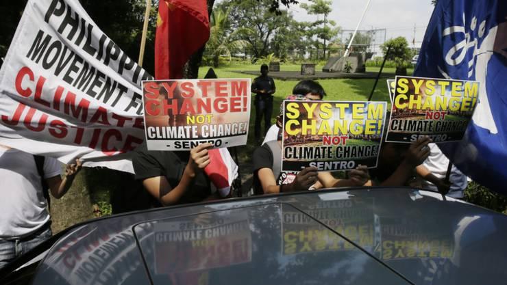 """Umweltaktivisten demonstrieren in Quezon, nordöstlich der philippinischen Hauptstadt Manila. Die Philippinen gehören zu den 20 Staaten, die sich in Lima zur Gruppe der """"V20"""" zusammengeschlossen haben (Archiv)"""