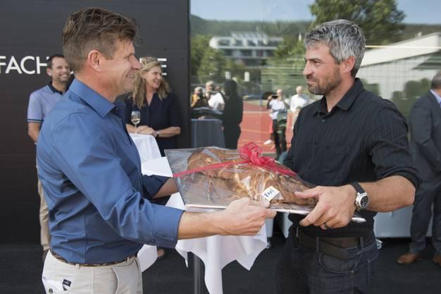 Gemeinderat Martin Egloff (FDP) übergibt den Schlüssel aus Zopfteig an Bildungsvorsteher Sandro Sozzi (CVP).