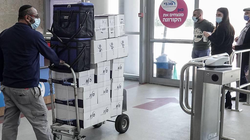 Eine Person mit Mund-Nasen-Schutz bringt Kartons mit dem Corona-Impfstoff von Pfizer-Biontech in die Pais Arena. Foto: Nir Alon/ZUMA Wire/dpa
