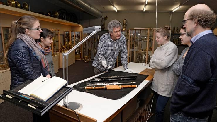 Adrian von Steiger (Mitte), Leiter der «Klingenden Sammlung», erklärt Musikstudentinnen Querflöten aus verschiedenen Epochen.