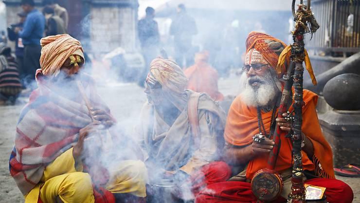 Vor dem Pashupati-Tempel in Kathmandu versammeln sich Sadhus - als heilig angesehene Männer -, um dort die ganze Nacht zu beten und zu meditieren.