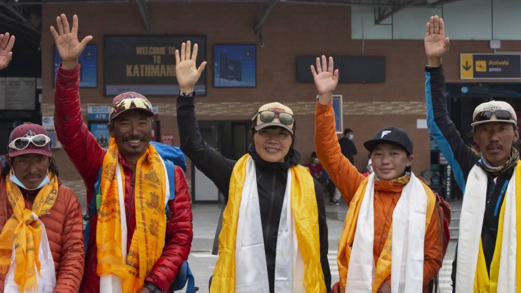 Tsang Yin-hung (M) aus Hongkong winkt während einer Pressekonferenz anlässlich ihres aufgestellten Rekordes für den Aufstieg des Mount Everest. Foto: Bikram Rai/AP/dpa