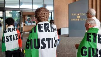 """Verwandte von Asbest-Opfern, eingehüllt in italienische Flaggen mit dem Schriftzug """"Eternit Giustizia"""" (zu deutsch etwa: """"Gerechtigkeit im Eternit-Fall""""), vor dem Turiner Justizpalast. (Archiv)"""