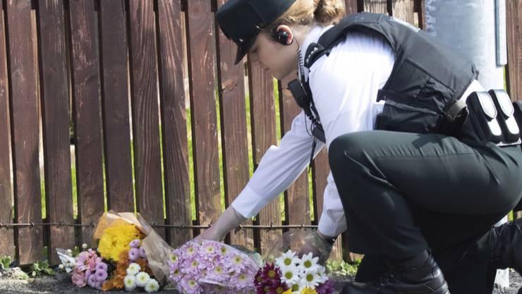 Eine Polizistin legt am Ort Blumen nieder, an dem in Derry eine 29-jährige Journalistin getötet wurde. Die Polizei meldete am Samstag die Festnahme von zwei Verdächtigen.