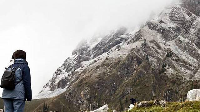 Eine Frau betrachtet das verschneite Säntisgebirge