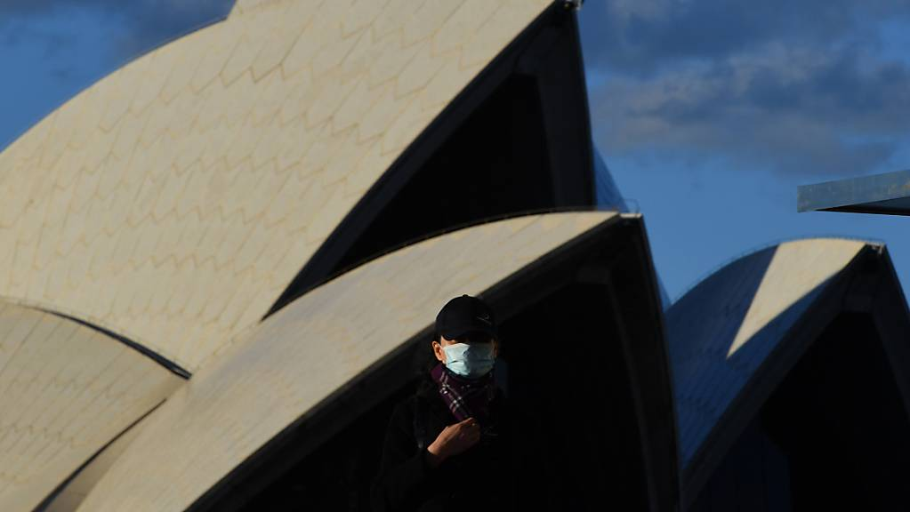 A pedestrian wearing a mask walks past the Sydney Opera House in Sydney, Saturday, June 26, 2021. All of greater Sydney, the Central Coast, the Blue Mountains and Wollongong regions will enter a two-week coronavirus lockdown until 9 July and new restrictions will be in place for the remainder of New South Wales. (AAP Image/Mick Tsikas) NO ARCHIVING
