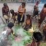 In Westpapua wird für ein Festmahl ein in Bananenblätter eingewickeltes Schwein in einer Erdgrube gegart.