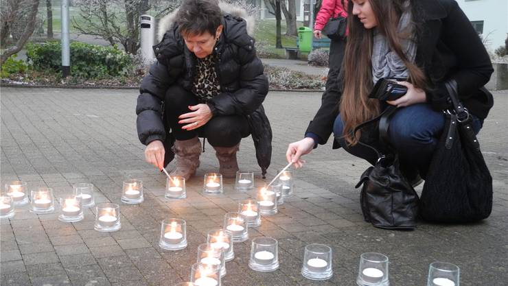 Zwei Passantinnen zünden vor dem Spital eine Kerze an. DBI