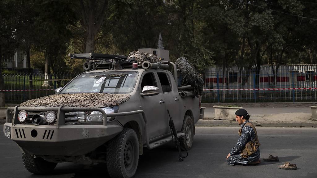 Ein Kämpfer der Taliban betet auf der Straße neben einer von der afghanischen Gesellschaft der muslimischen Jugend organisierten Demonstration, bei der die Freigabe von eingefrorenen internationalen Geldern gefordert wird. Foto: Bernat Armangue/AP/dpa