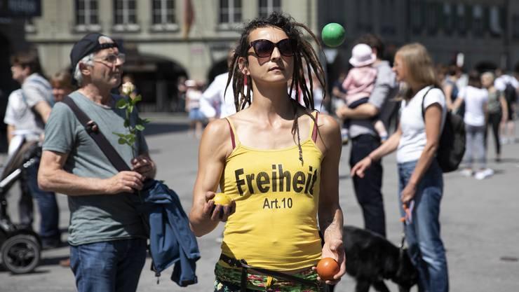 Eine Demonstrantin jongliert an einer Demonstration gegen den Lockdown in Bern.
