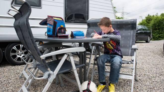 Ein jenischer Knabe löst auf einem Stellplatz in Kaiseraugst AG Aufgaben für die Schule. Foto: Jiri Reiner