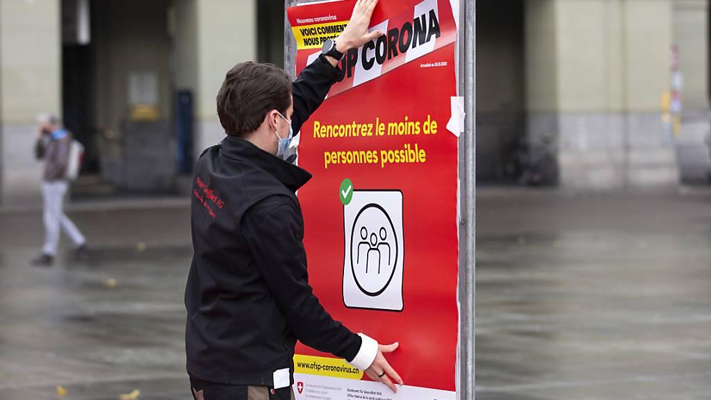"""Coronavirus: Ein neues rotes BAG-Plakat mit der Verhaltensregel """"Treffen Sie so wenige Menschen wie möglich""""wird auf dem Bundesplatz in Bern installiert."""