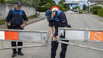Beamte des Eidgenössischen Grenzwachtkorps entfernen eine Absperrung bei der Grenze zu Frankreich.