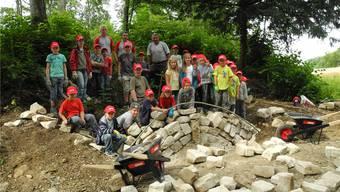 Stolz posieren die Ferienpasskinder mit der Brücke aus Natursteinen, die schon vor dem Mittag ansehnliche Ausmasse erreicht hatte.