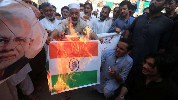 Aufgebrachte Menschen verbrennen die indische Flagge und protestieren dagegen, dass Indien die Autonomie für Kaschmir aufhebt.