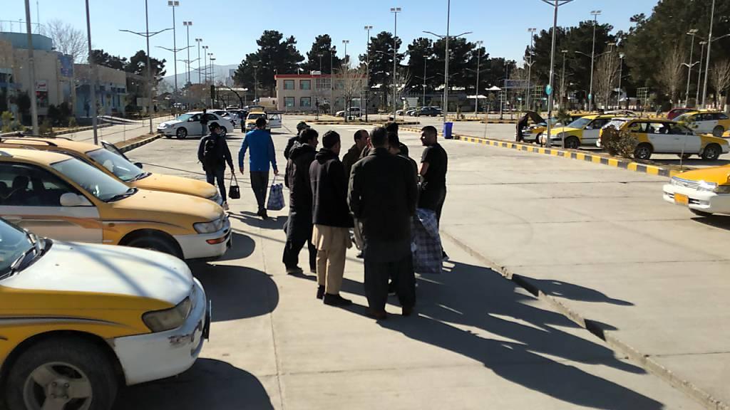 Durch einen Abschiebeflug deportierte Afghanen verhandeln vor dem Flughafen mit Taxifahrern den Preis für die Weiterreise. Nach Monaten der Unterbrechung durch die Corona-Pandemie hat Deutschland die Sammelabschiebungen nach Afghanistan wieder aufgenommen. Foto: Qiam Noori/dpa