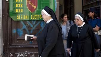 Wählerinnen verlassen in Rom ein Abstimmungslokal