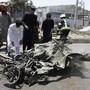Menschen in Kabul sehen sich das Wrack des Autobombers an.