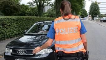 Eine Polizistin hält einen Autofahrer an, der das Fahrverbot im Quartier missachtete