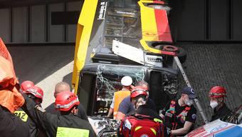 Einsatzkräfte arbeiten an einer Unfallstelle eines Linienbusses, der von einer Überführung  einer Autobahn über eine Schnellstraße abgestürzt ist. Bei dem Sturz sei mindestens ein Mensch ums Leben gekommen, 21 weitere verletzt. Foto: Pawel Supernak/PAP/dpa