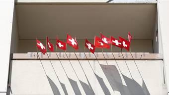 Schweizer Fahnen haengen am Balkon eines Wohnblocks. (Symbolbild)