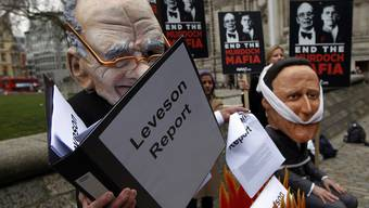 Aktivisten, maskiert als Rupert Murdoch (l.) und David Cameron, kritisieren Camerons Haltung zum Leveson-Bericht