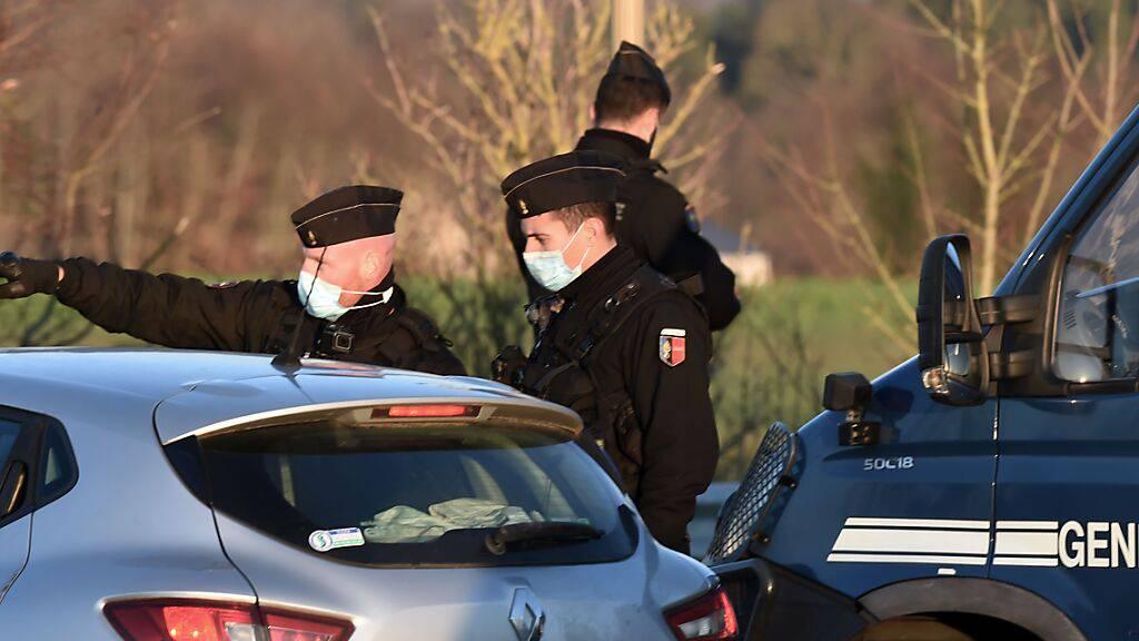 Gendarme blockieren den Zugang zum Veranstaltungsort einer Party. In Frankreich haben sich zum Jahreswechsel Tausende auf mehreren illegalen Großpartys getroffen. Foto: Jean-Francois Monier/AFP/dpa