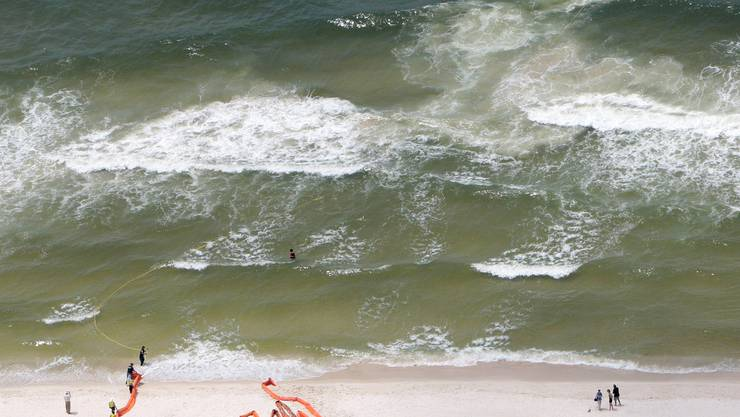 Oil cleanup workers work with oil retention booms on the beach in Gulf Shores, Ala., Saturday, June 5, 2010. Oil from the Deepwater Horizon disaster has started washing ashore on the Alabama and Florida coast beaches. (AP Photo/Dave Martin)