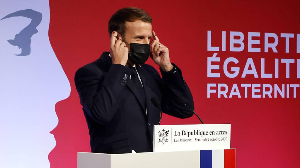 Emmanuel Macron, Präsident von Frankreich, zieht seine Maske an, nachdem er in Les Mureaux eine Rede gehalten hat. Frankreich will nach den islamistischen Terroranschlägen mit vielen Toten in den vergangenen Jahren verstärkt gegen Radikalisierung vorgehen. Foto: Ludovic Marin/POOL AFP/dpa