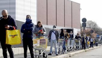 Kundinnen und Kunden warten vor einem Supermarkt in Italien auf Einlass.