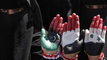Jemenitische Demonstrantinnen zeigen ihre bemalten Hände: Flaggen von Libyen vor der Gaddafi-Ära, Jemen und Syrien (v. l.)