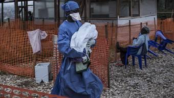 Eingesundheitsmitarbeiter bringt ein vier Tage altes Baby, das wahrscheinlich an Ebola erkrankt ist, in ein Behandlungszentrum. (Archiv)