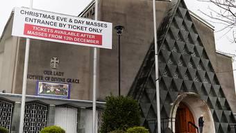 Vor der Kirche Our Lady Mother of Divine Grace weist ein Schild darauf hin, dass der Eintritt zu den Weihnachtsgottesdiensten nur mit einer Eintrittskarte möglich ist. Foto: Brian Lawless/PA Wire/dpa