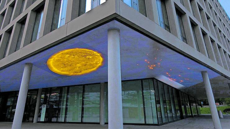 Eine Visualisierung zeigt, wie die Kunstprojektion unter das Vordach des Campus-Aussenbereichs aussehen könnte.