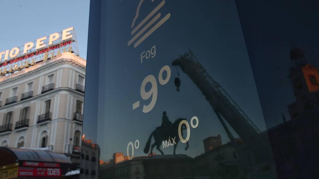 Ein Bildschirm an der Puerta del Sol in Madrid zeigt eine Temperatur von minus 9 Grad an.