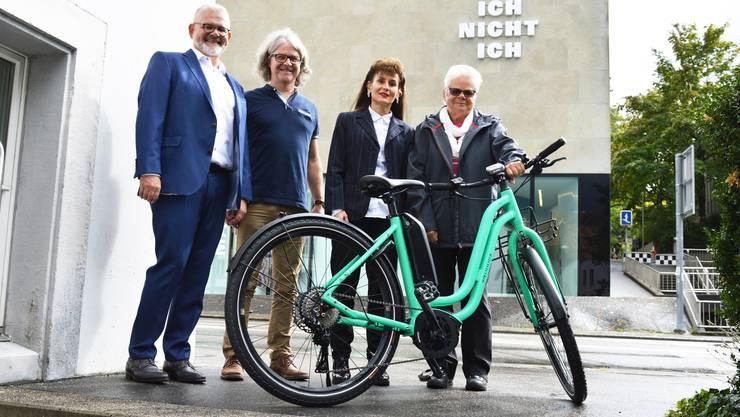 Preisübergabe: Anna Rickli (rechts) posiert mit ihrem neuen E-Bike, das ihr Regula Kiechle (zweite von rechts) vom Aargauer Roten Kreuz und Markus Schumacher (links) von der Pro Senectute Aargau übergeben haben, vor dem unterwegs.ch-Laden von Stefan Lienhard (zweiter von links).