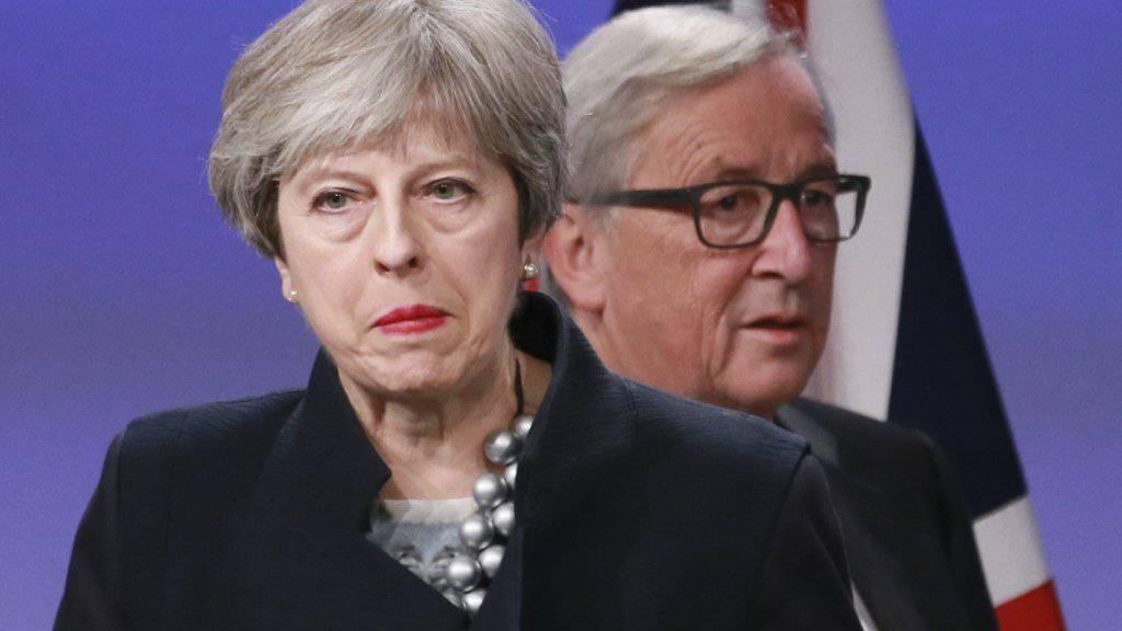 Not amused - aber sie dürfen es sich nicht anmerken lassen. EU-Kommissionspräsident Juncker (hinten) gibt sich in Brüssel vor Journalisten jedenfalls optimistisch, ebenso die britische Premierministerin May.