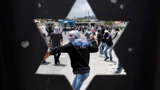 Junge Palestinenser werfen Steine gegen Polizisten in Ras al-Amud