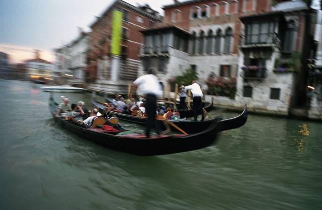 Gondolieri rudern Touristen durch die Kanäle von Venedig.