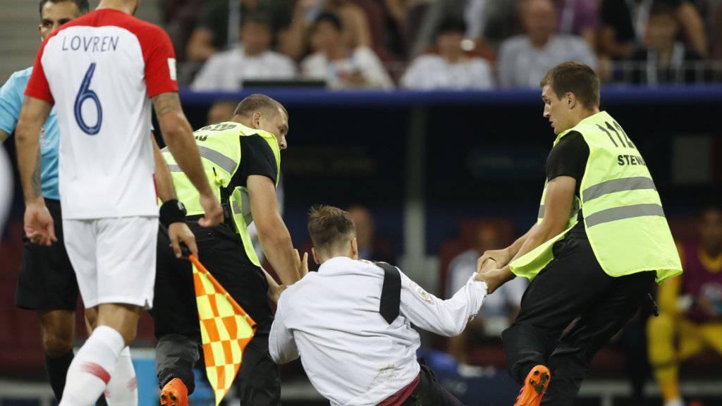 Ein WM-Flitzer wird von Ordnungshütern vom Platz gezerrt