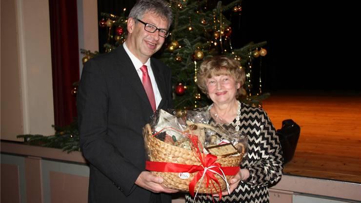 Ein Geschenk vor dem Weihnachtsbaum: Daniel Mosimann überreicht Marianne Tribaldos einen Früchtekorb.