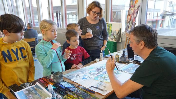 Die Ausstellungsbesucher dürfen den Maler Wilhelm Fikisz bei seiner Arbeit beobachten und ihm Fragen stellen.