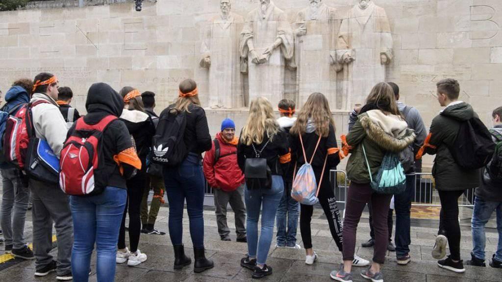 Die jugendlichen Protestanten und Protestantinnen aus der ganzen Schweiz informieren sich bei der Mauer der Reformatoren in Genf über die Rolle der Stadt während der Reformationszeit.