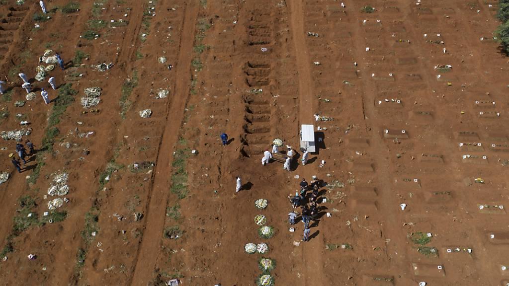 Friedhofsarbeiter tragen auf dem Friedhof Vila Formosa in Sao Paulo einen Sarg. Foto: Andre Penner/AP/dpa