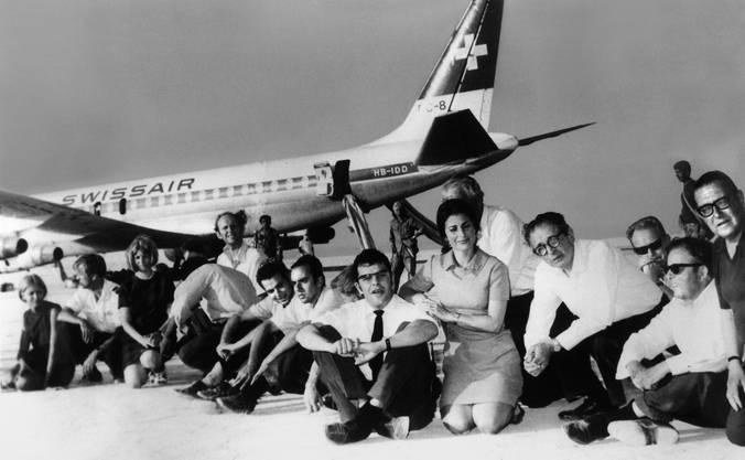 Jean Michel Weiss (Mitte, mit Krawatte) sitzt neben Beta Steinegger (Mitte, kniend) und weiteren Geiseln vor der entführten Swissair-Maschine. Das Foto entstand bei der Pressekonferenz, welche die palästinensischen Entführer organisiert hatten. Weiss und Steinegger mussten über die Zustände an Bord informieren. Bild: Keystone