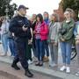 Ein Polizist bittet Demonstrantinnen in Minsk, den Ort zu verlassen. Foto: Dmitri Lovetsky/AP/dpa