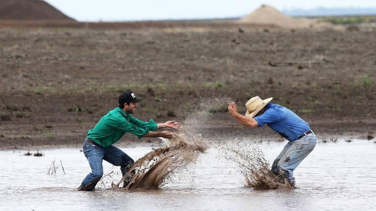 Zwei Bauern im Bundesstaat New South Wales freuen sich, dass ihre Felder von den lang ersehnten Regenfällen gewässert wurden.
