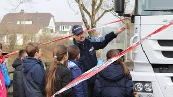 Polizist Rolf Urech zeigt den Schülerinnen und Schülern, wo bei einem Lastwagen der tote Winkel ist. zvg