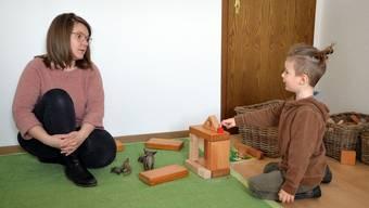 Kursleiterin Naturspielgruppe und Vorstandsmitglied Ramona Altermatt im Gespräch mit einem spielenden Knaben.